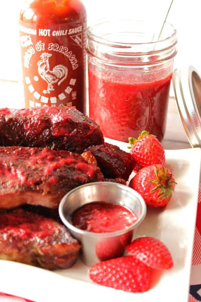 A closeup vertical photo of ribs on a plate with strawberry bbq sauce in the background.