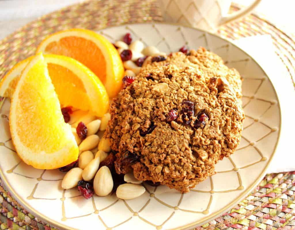 Overhead photo of gluten-free breakfast cookies on a plate with orange slices, almonds, and dried cranberries.