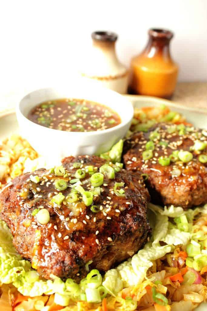 Closeup photo of a crispy duck patty on a plate with orange dipping sauce, scallions, and sesame seeds.