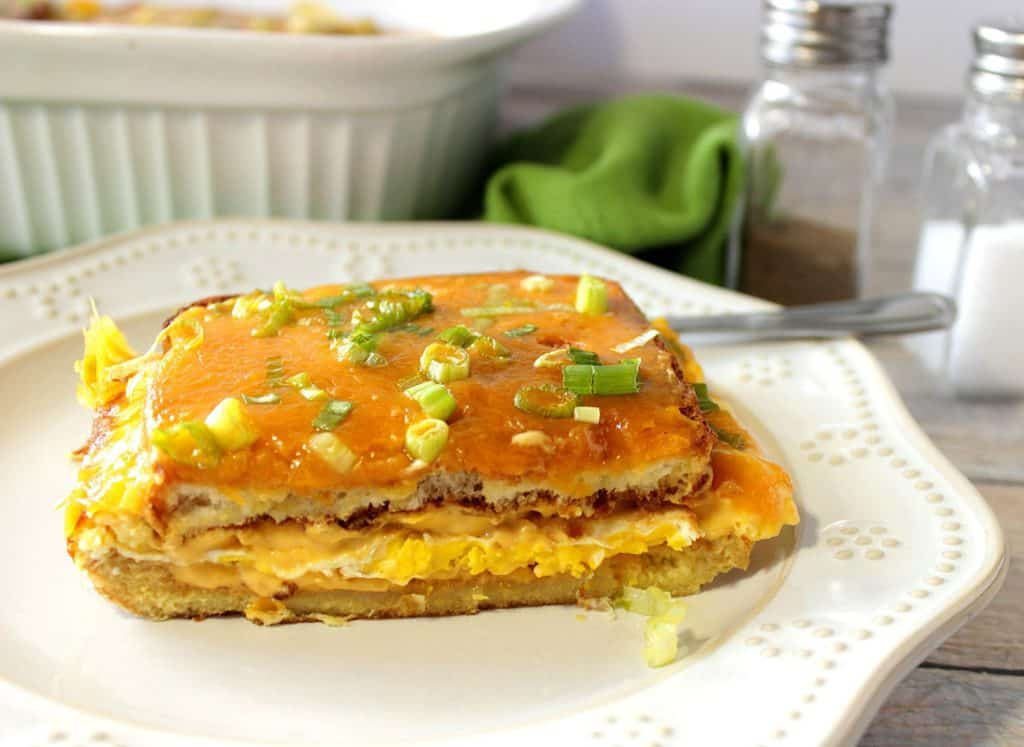 A slice of Egg Sandwich Casserole on a white plate with scallions and cheddar cheese.