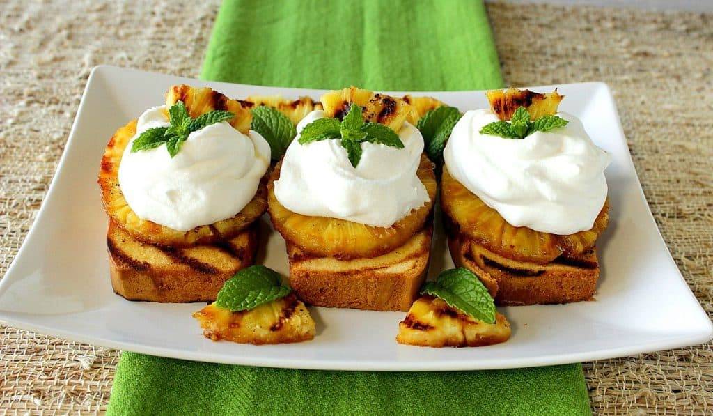 Three slices of grilled pineapple pound cake on a white plate with a green napkin and mint sprigs.
