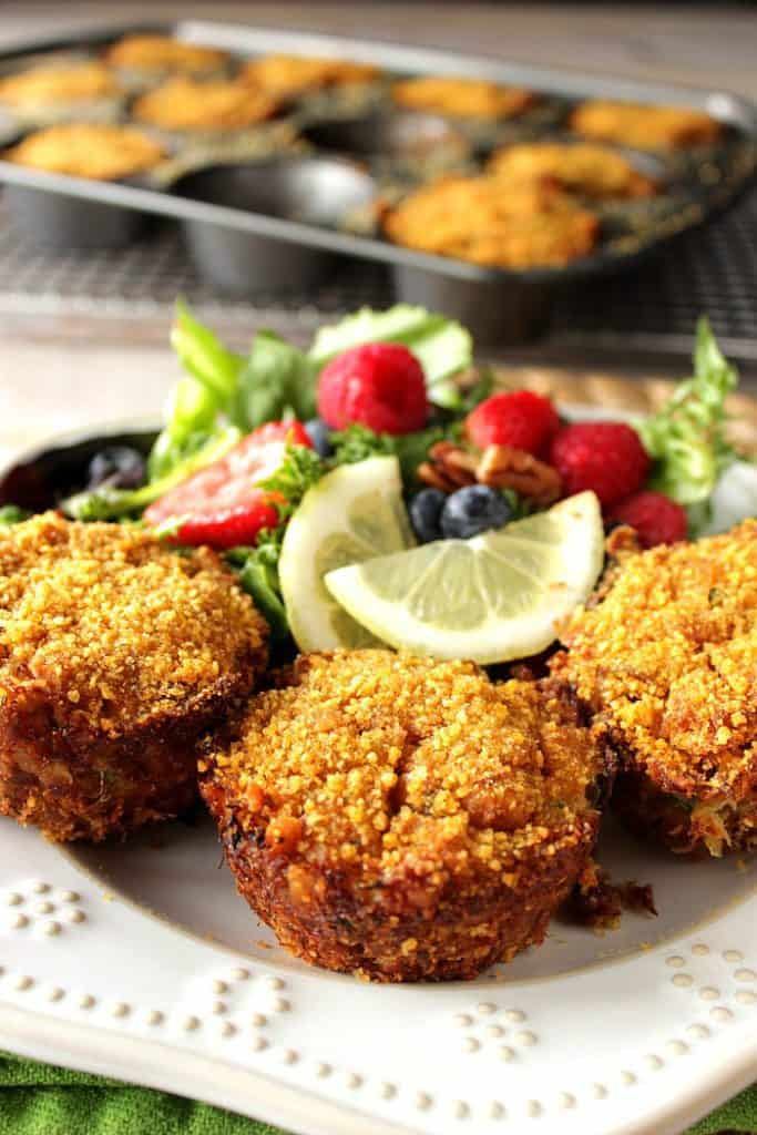 Meaty Cornflake Muffin Tip Crab Cakes on a plate with a salad and berries in the background.