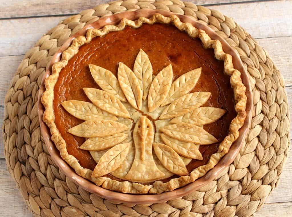 Overhead photo of a Turkey Crust Pumpkin Pie on a rattan place mat.