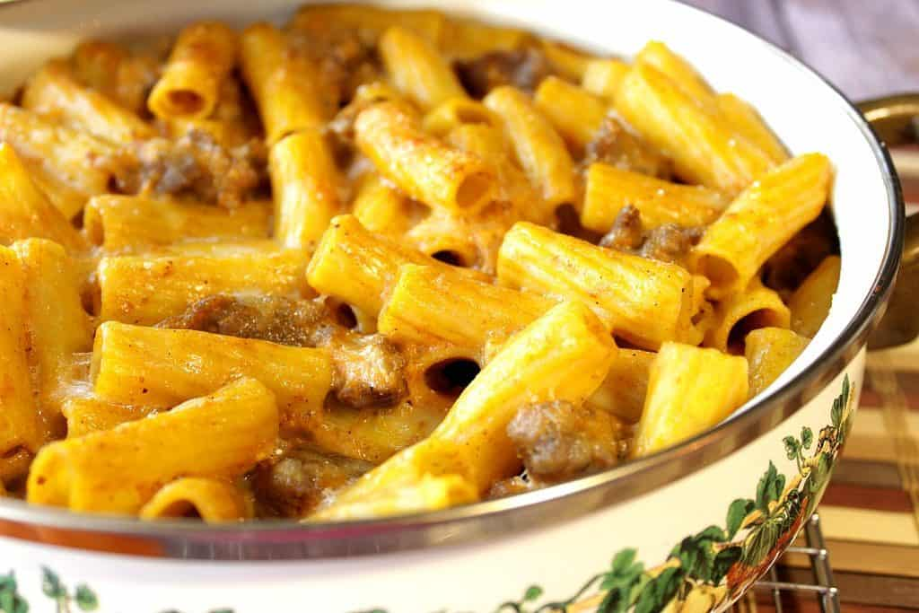 An offset horizontal photo of a casserole dish filled with pumpkin cream pasta with bratwurst