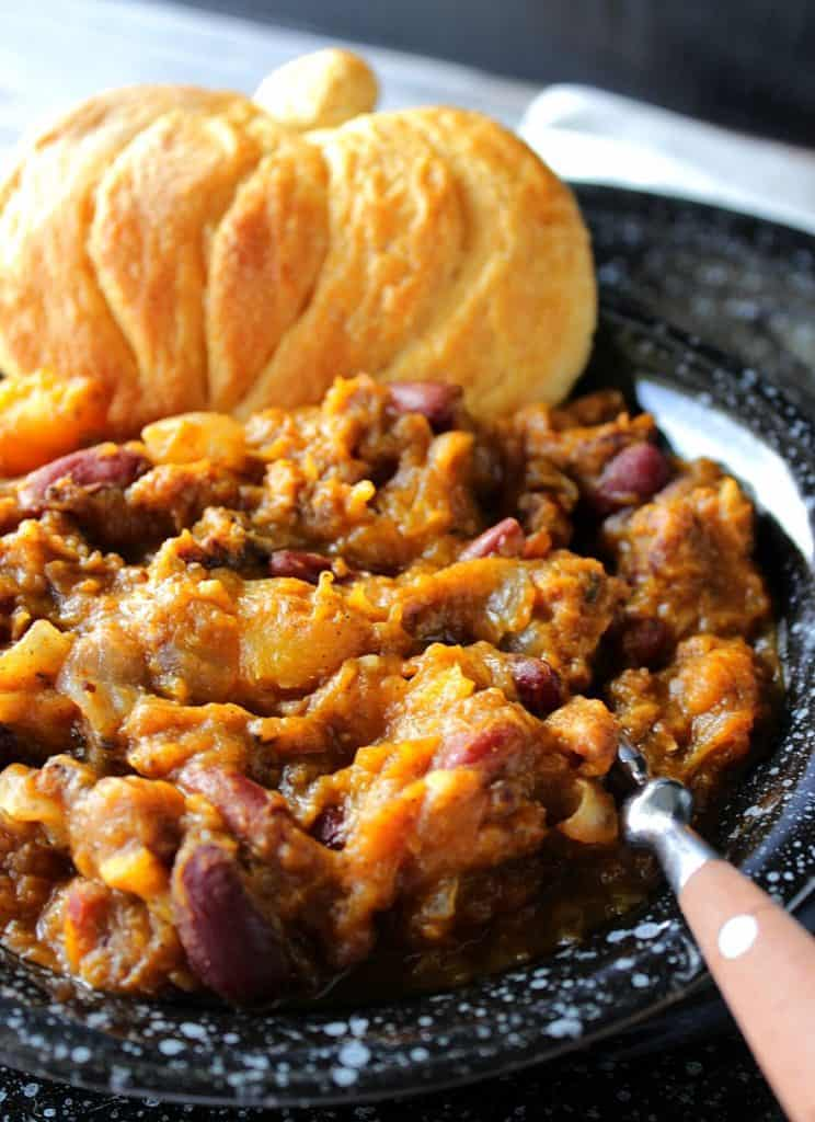 Closeup vertical photo of Slow Cooker Butternut Squash Chili with a pumpkin shaped biscuit.