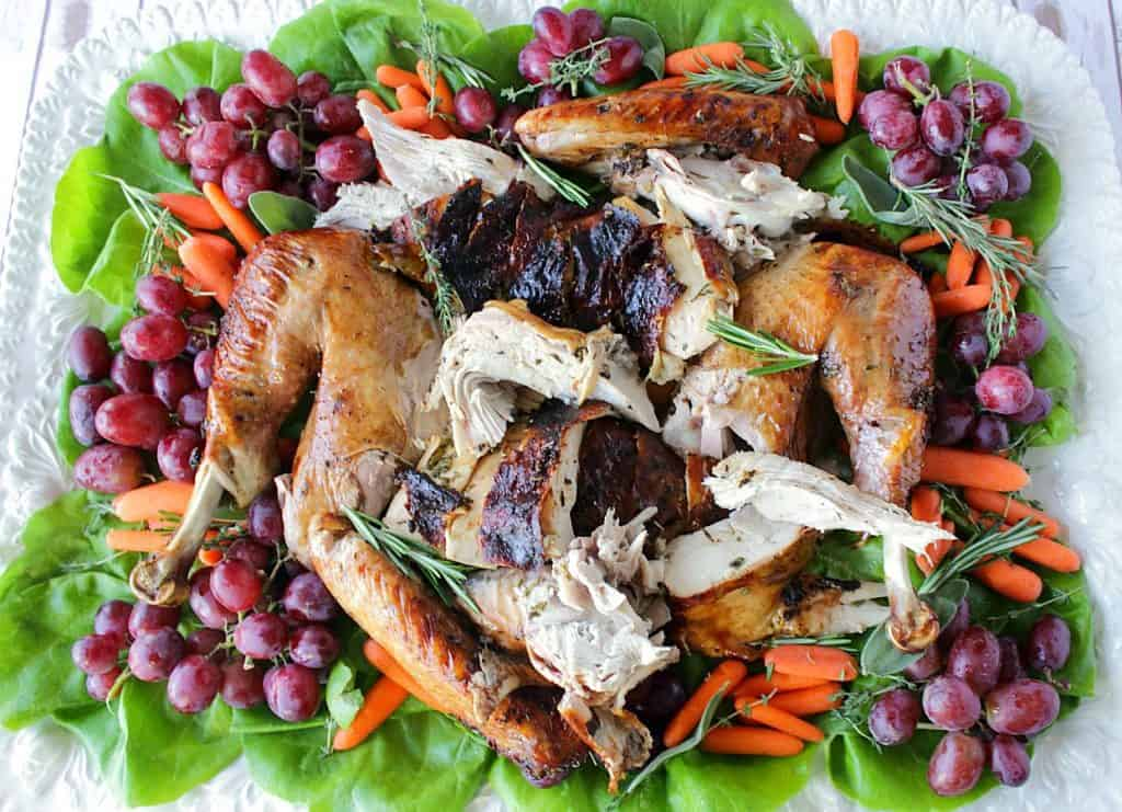 An overhead horizontal photo of a white platter filled with sliced, roasted turkey along with grapes, carrots, herbs, and greens.