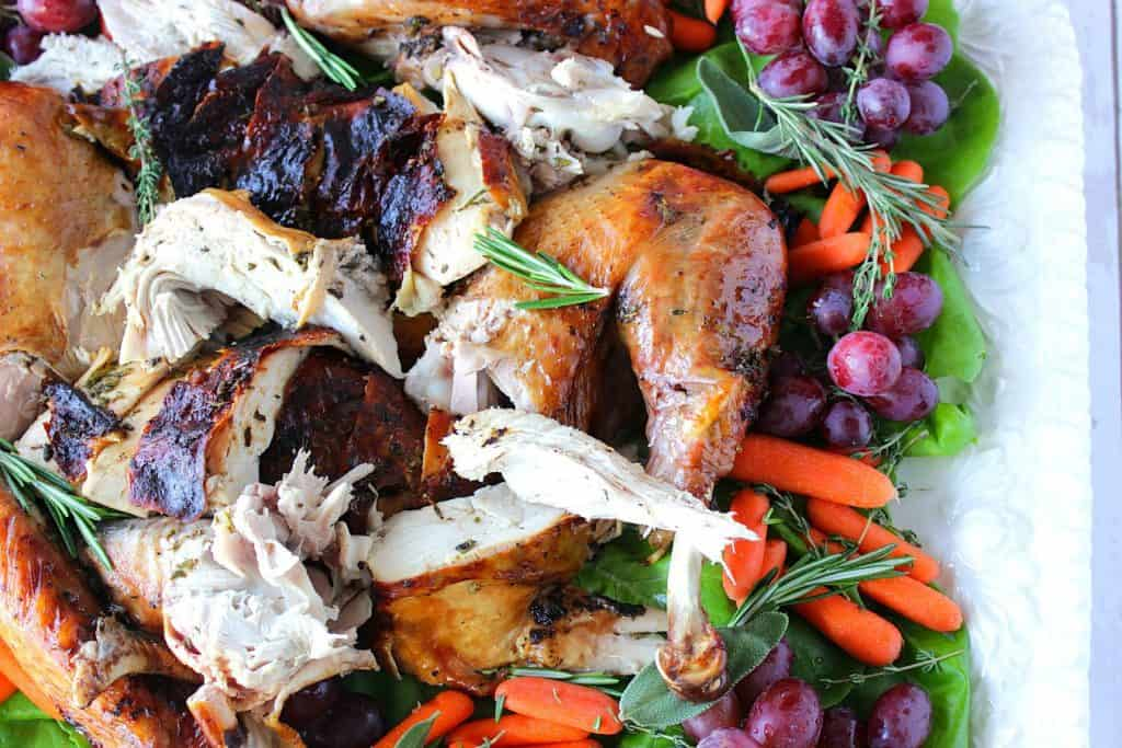Overhead photo of a sliced balsamic and herb roasted turkey on a platter with herbs, grapes and carrots.