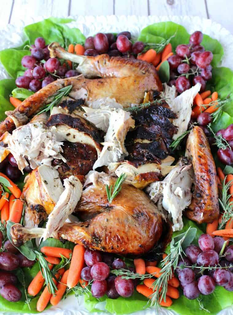 A vertical photo of a colorful platter of a balsamic herb roast turkey which is sliced and surrounded by grapes, carrots, herbs, and greens.