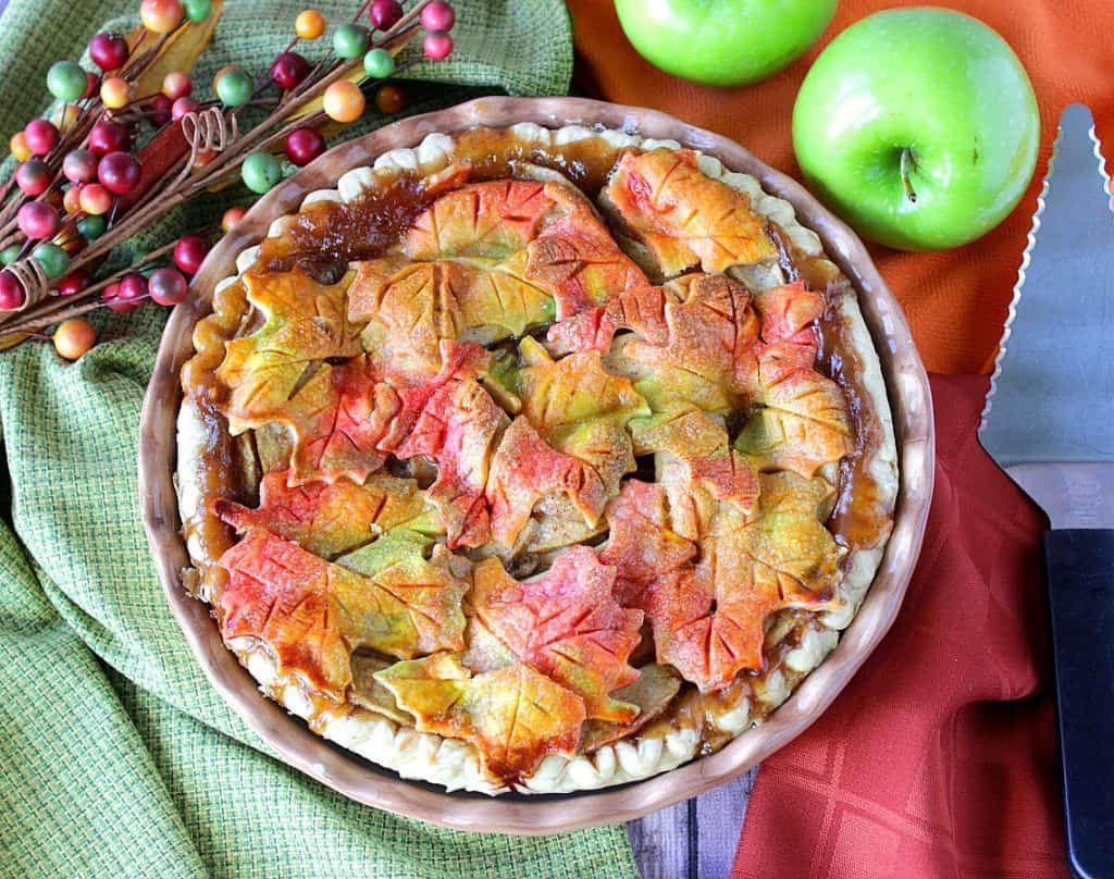 Overhead photo of a pie pan with an autumn leaves apple pie, colorful napkins, a pie server, and apples.