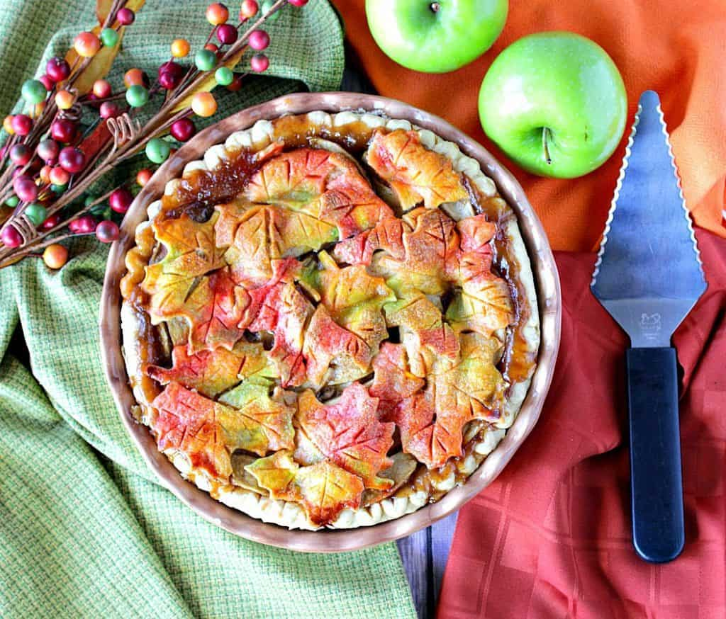 Overhead photo of an autumn leaves apple pie with a pie server and apples.