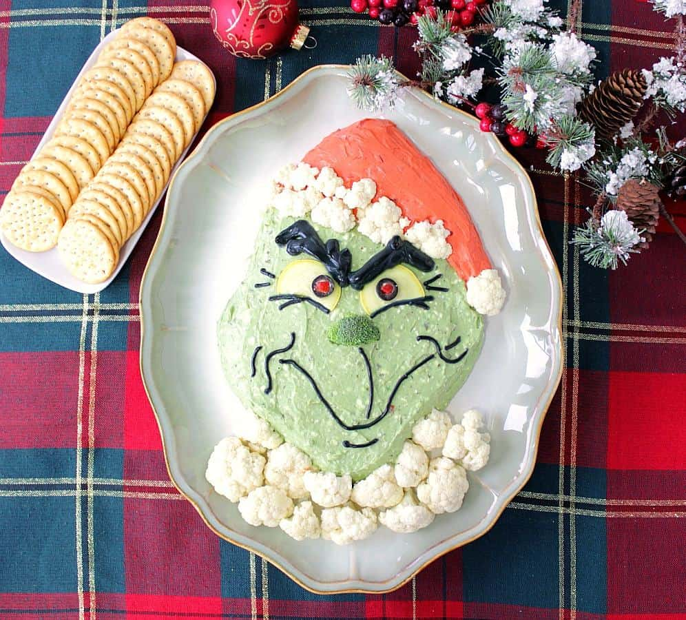 Realistic Looking Grinch Guacamole on a red and green plaid tablecloth with crackers.