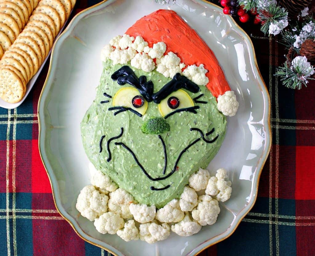 Overhead photo of a grinch guacamole on a plate with cauliflower fur and crackers.