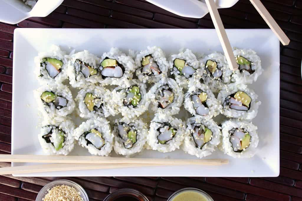Overhead picture Sushi Rolls with Avocado and Shrimp on a long white plate with sesame seeds and chopsticks.