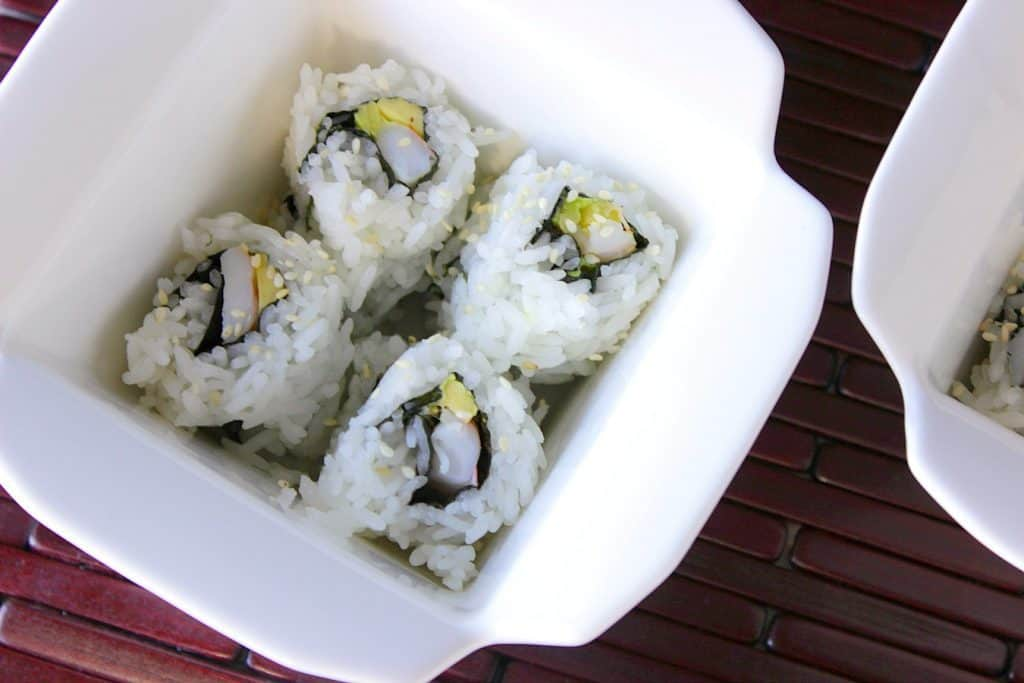 Closeup of Homemade Avocado Shrimp Sushi Rolls in a takeout container.