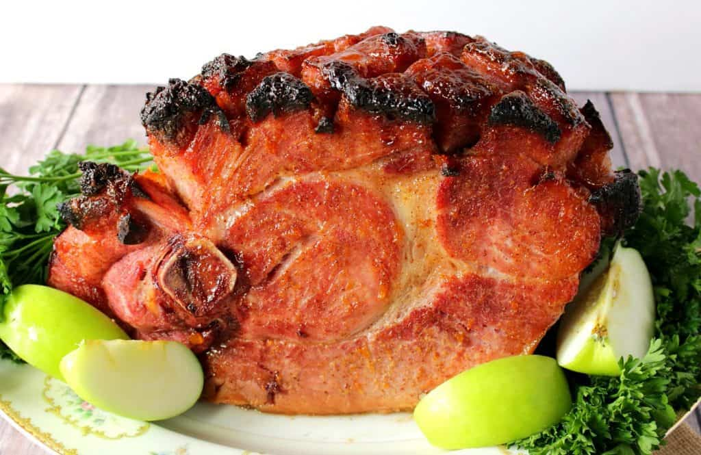 A horizontal photo of a whole glazed ham on a platter with apple wedges and parsley for garnish.