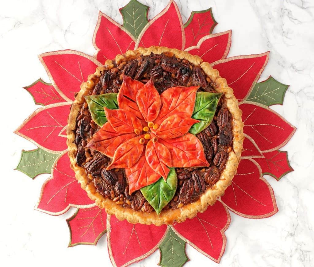An overhead horizontal photo of a pecan pie with a painted poinsettia pie crust on a red and green poinsettia place mat.