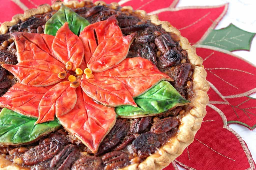 An offset horizontal closeup photo of a pretty poinsettia painted pecan pie on a poinsettia place mat.