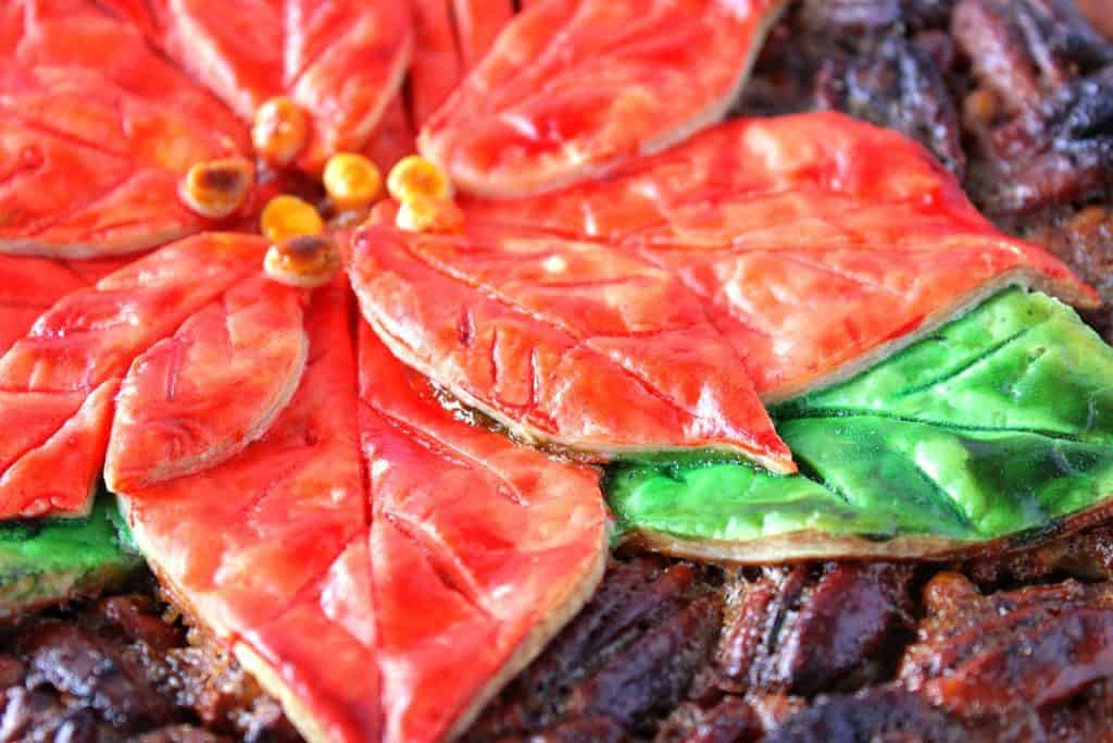 Horizontal closeup photo of a painted poinsettia pie crust with red and green petals.