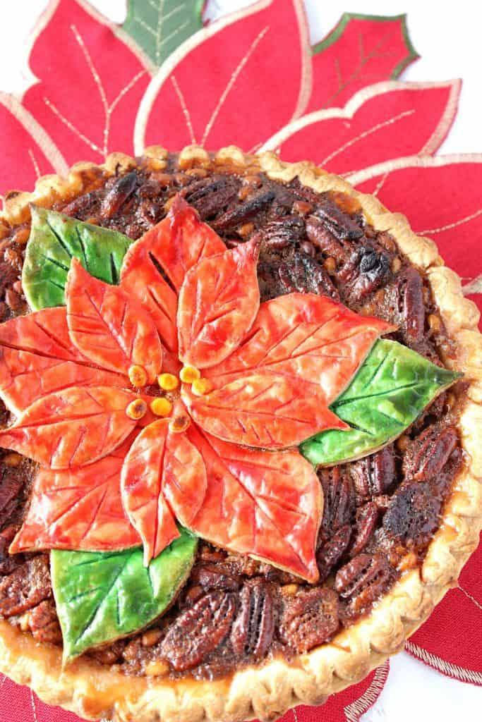 A vertical offside overhead and closeup photo of a pecan pie with a painted poinsettia crust on top.