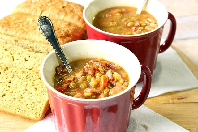Two mugs of Split Pea Soup with a loaf of bread and two spoons.