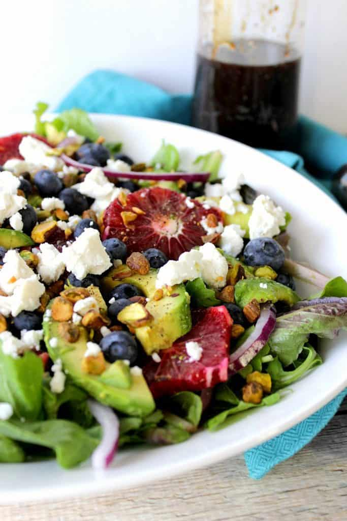 Antioxidant Rich Blood Orange Salad with Blueberries & Feta on a white plate with a blue napkin. - kudoskitchenbyrenee.com