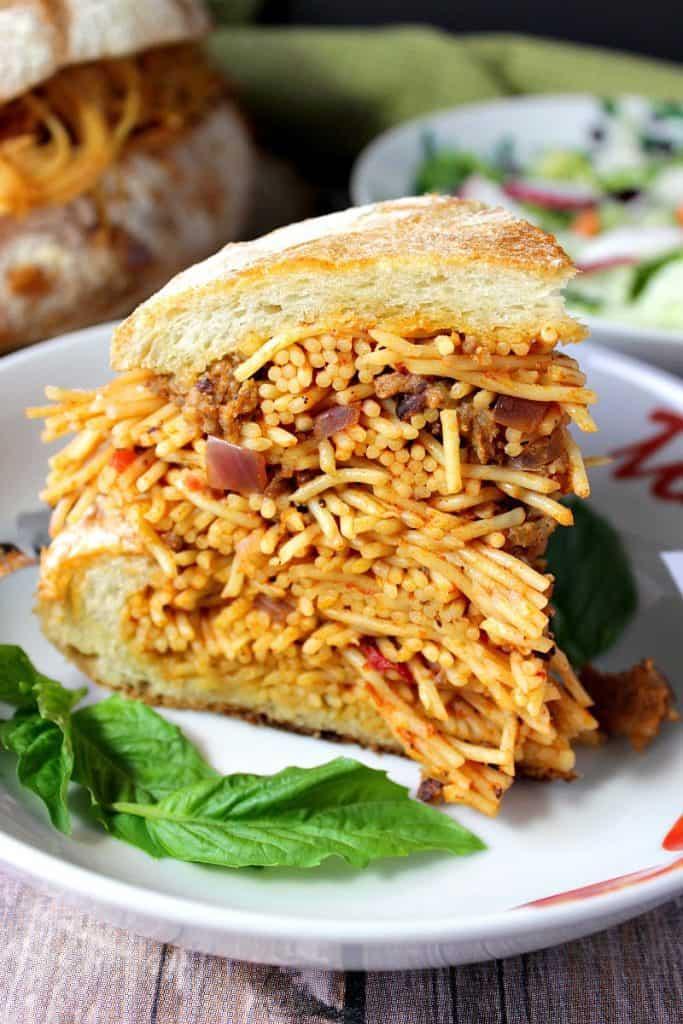 A closeup photo of a slice of Spaghetti Stuffed Garlic Bread