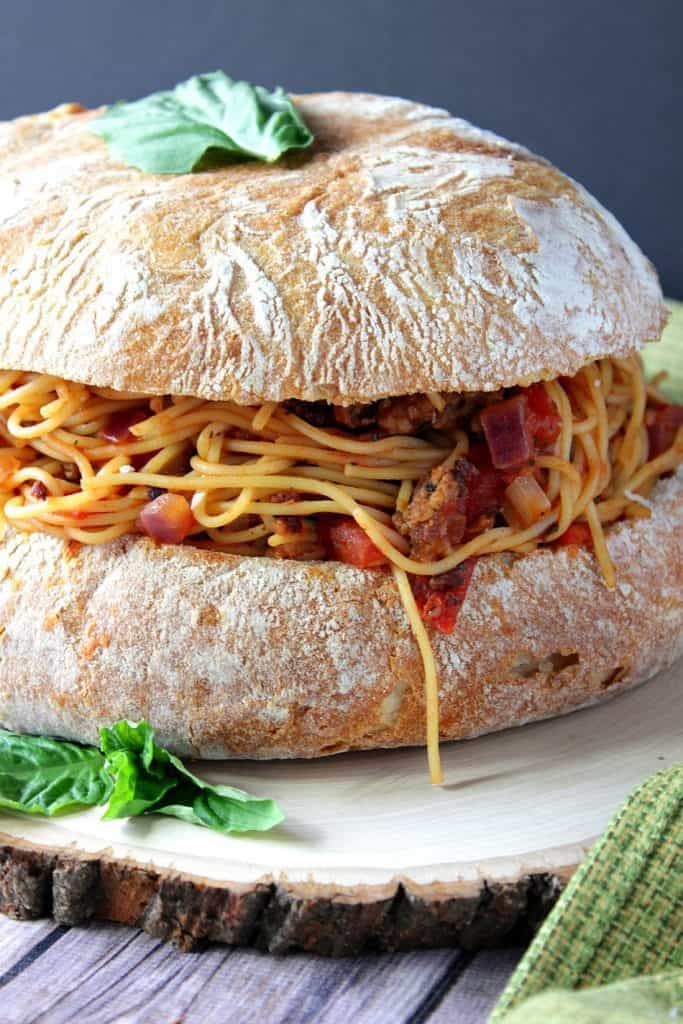 Closeup photo of spaghetti stuffed garlic bread with a fresh basil leave on top.