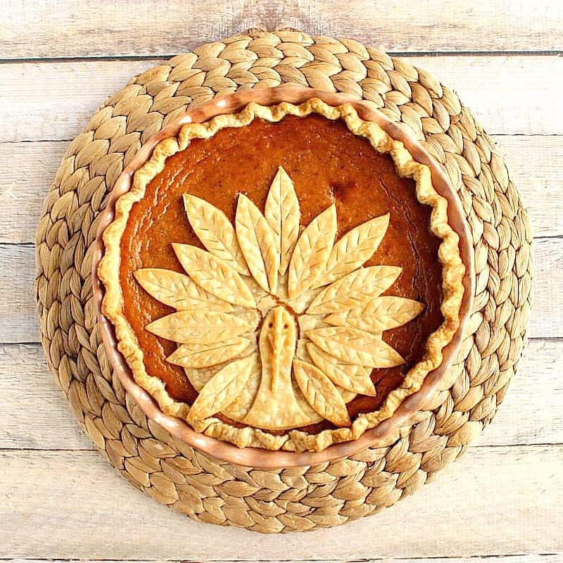 Directly overhead photo of a turkey crust pumpkin pie on a round rattan place mat.