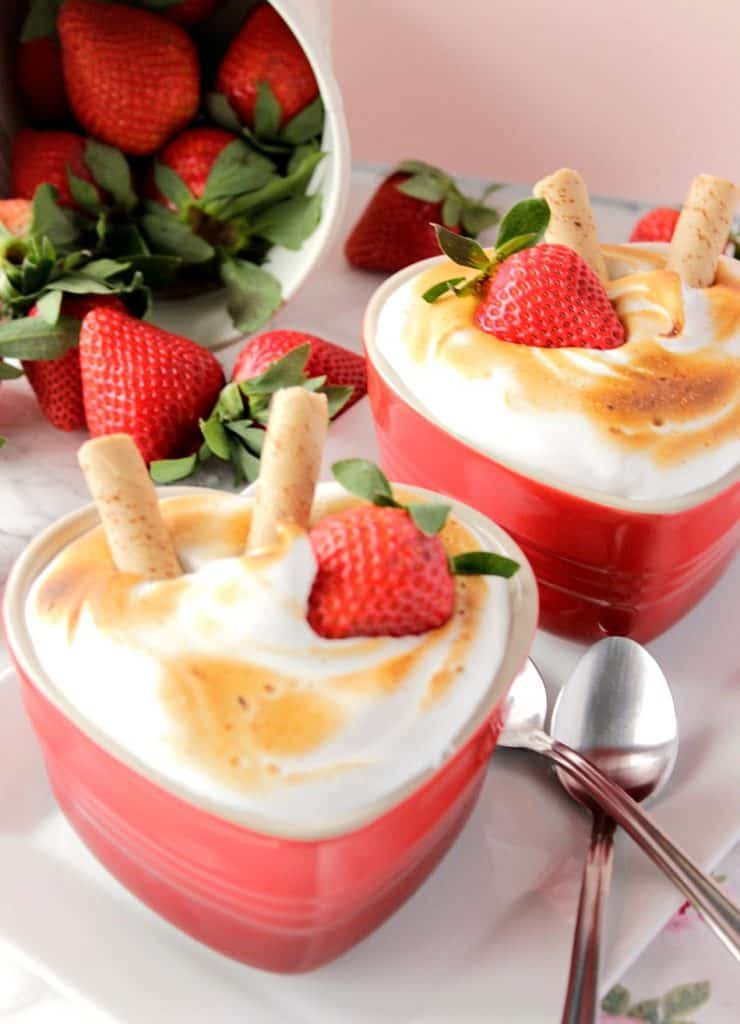 Baked Alaska for Two on a white plate with a fallen bucket of strawberries in the background..