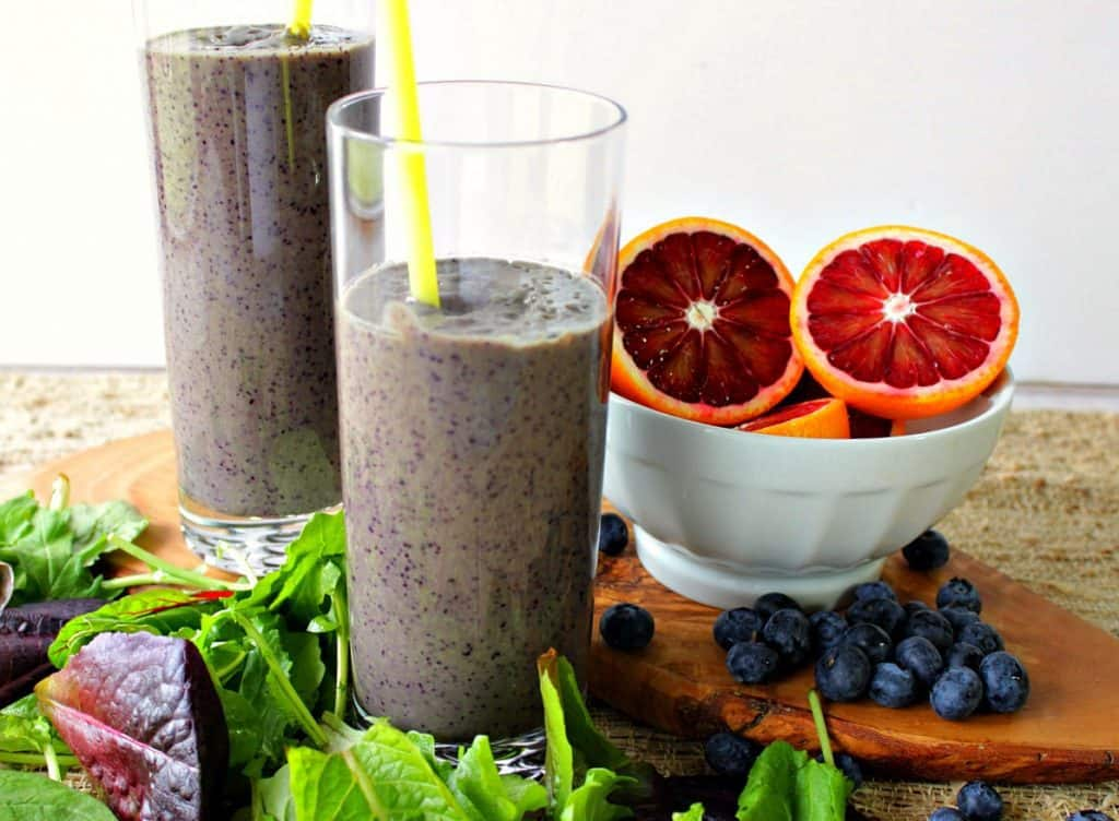 Two glasses of blood orange smoothies with assorted lettuces on a wooden board.