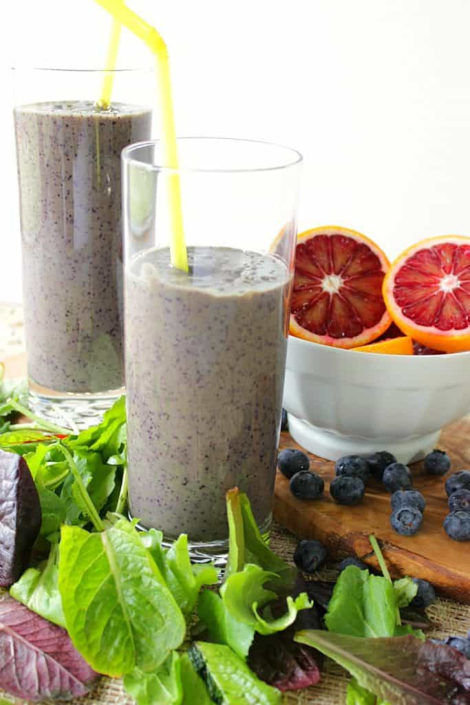 2 blood orange blueberry breakfast smoothies with straws and a bowl of cut oranges