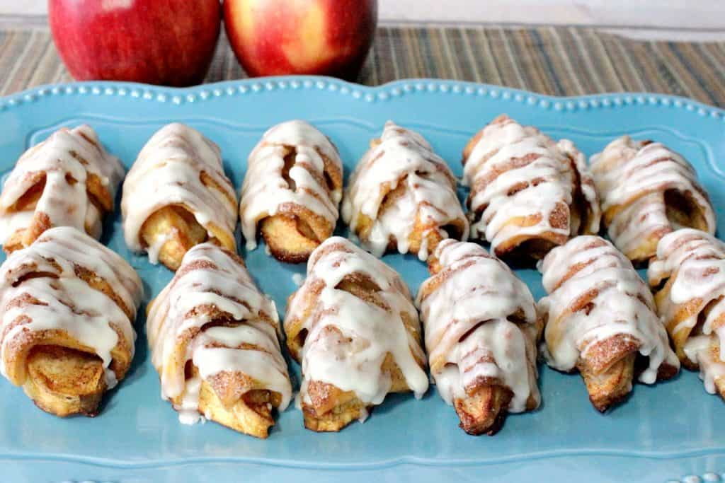 A horizontal photo of a blue plate of apple pie wedges with icing.