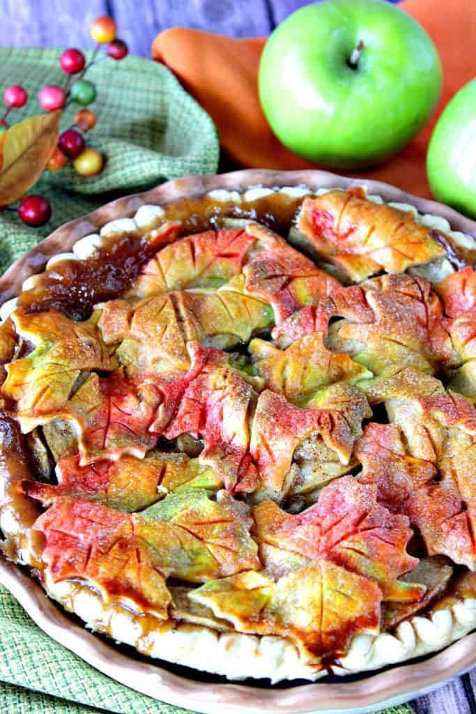 Closeup vertical image of Autumn Leaves Apple Pie with a colorful crust.