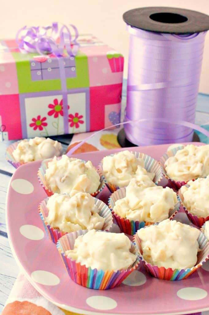 A vertical photo of a plate of tropical white chocolate candy with a gift wrapped package and a roll of ribbon in the background.