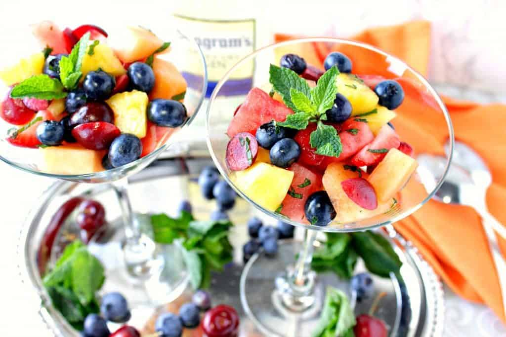 Overhead photo of two martini glasses filled with colorful Boozy Fruit Cocktail