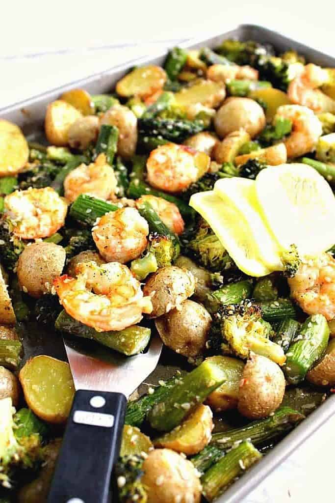 A sheet tray of shrimp, potatoes, asparagus and broccoli.