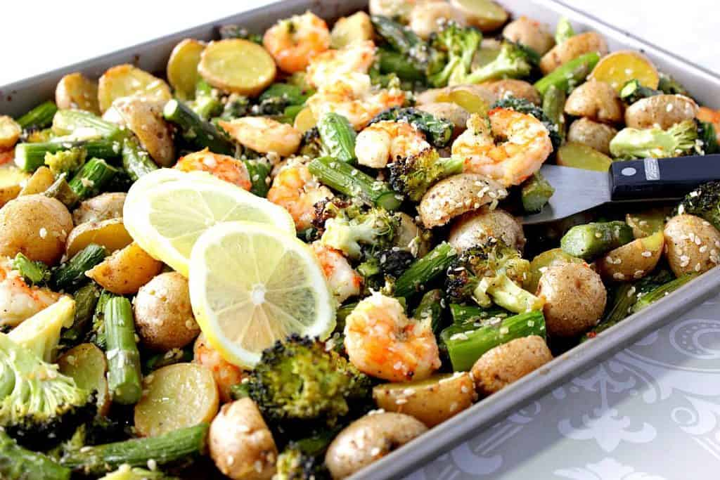 Sheet pan filled with broccoli, shrimp, asparagus and potatoes.