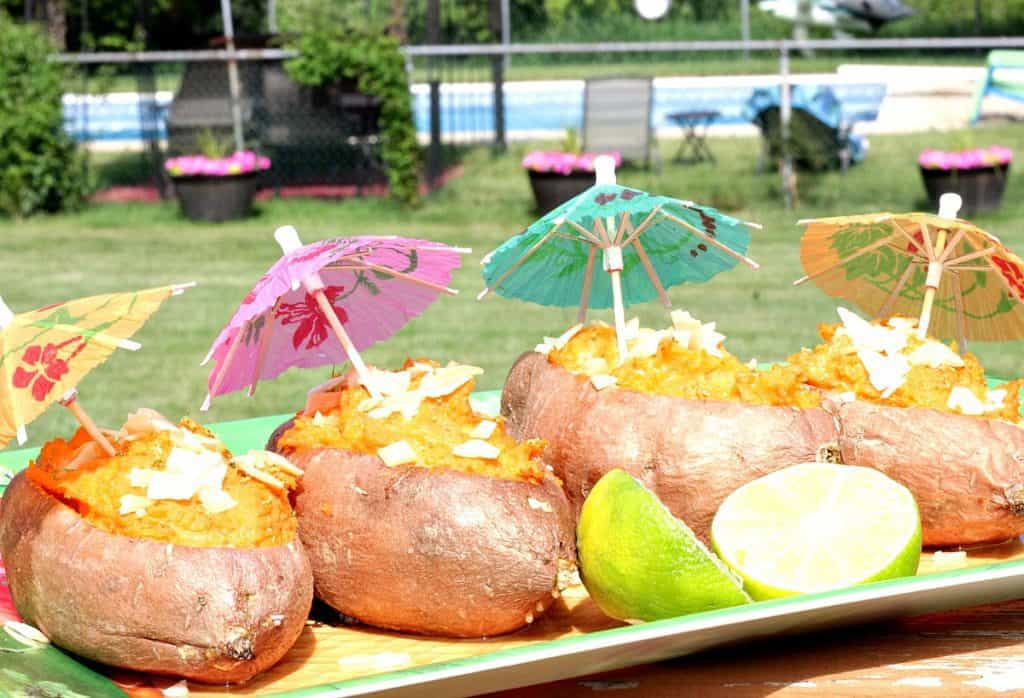 Outside photo of sweet potatoes on a tropical platter with paper umbrellas and a swimming pool in the background.