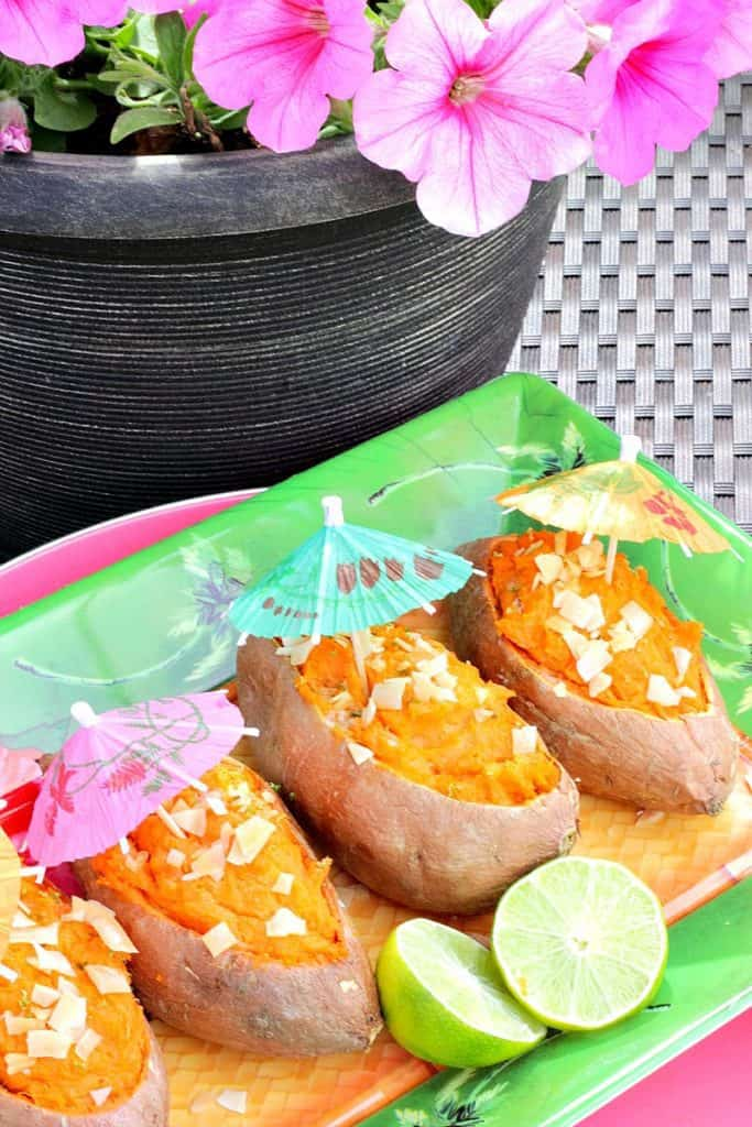Pink petunias in the background with sweet potatoes and paper umbrellas on a tropical plate.