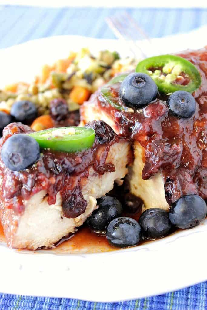 Closeup photo of a chicken breast on a white plate the blueberry BBQ sauce and sliced jalapenos.