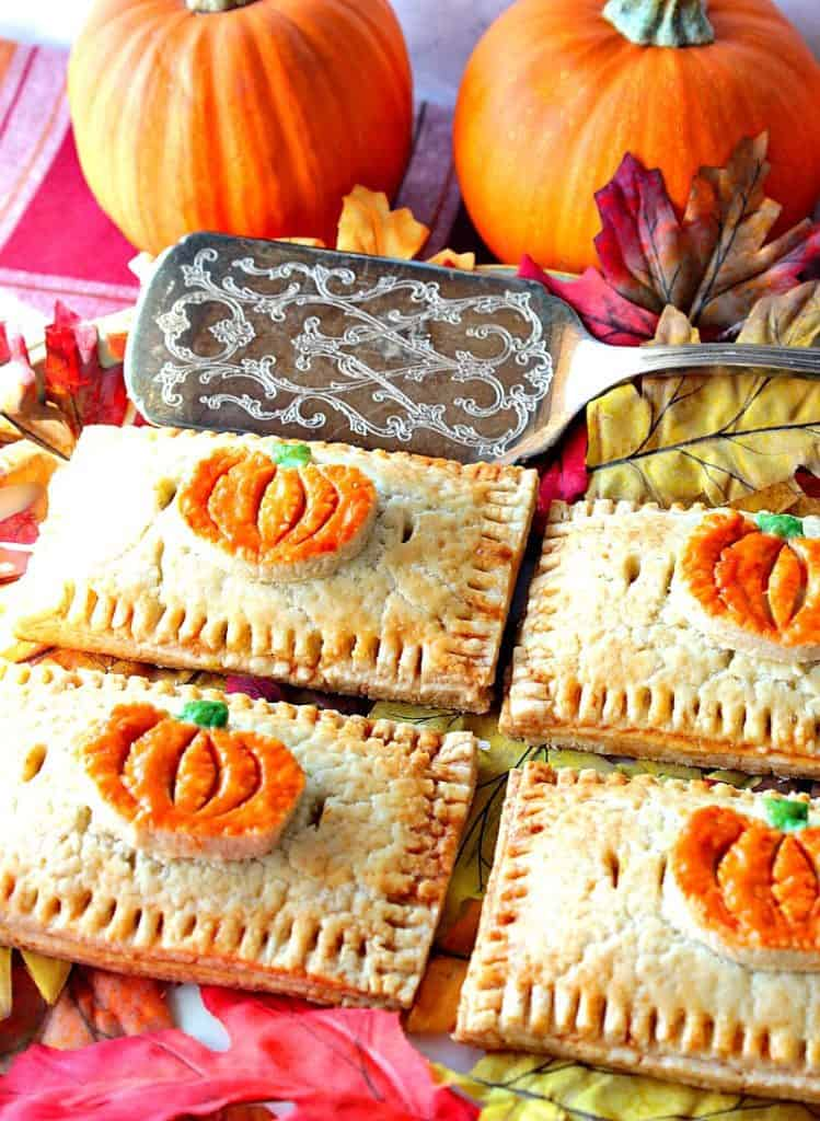 Pumpkin hand pies with pumpkin embellishments on a platter with a silver spatula, and autumn leaves.