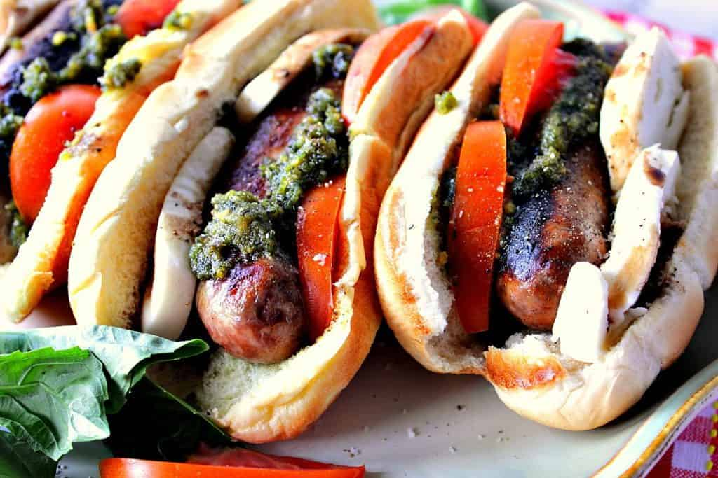 Three caprese sausage sandwiches on a platter with tomatoes, mozzarella cheese, and basil pesto.