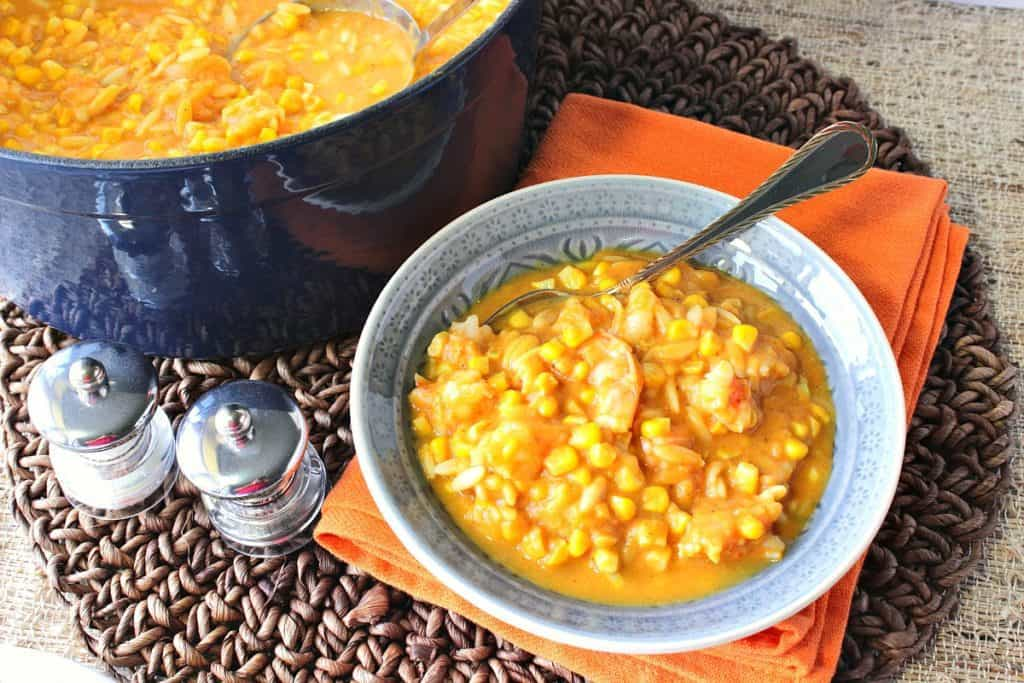 An overhead photo of a bowl of pumpkin corn chowder with a spoon and a blue pot with a ladle.