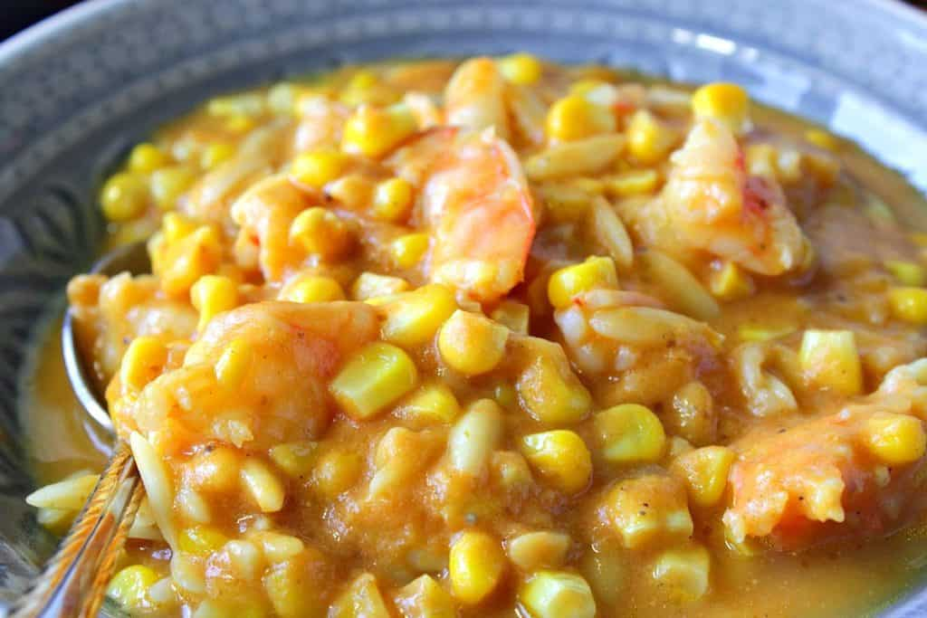 A closeup photo of corn chowder with pumpkin, orzo pasta and shrimp in a bowl.