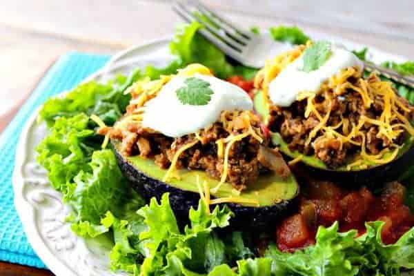 Two turkey taco stuffed avocado halves on a white plate with lettuce and salsa.
