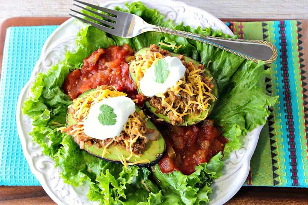 Two stuffed avocados on a plate with lettuce, salsa, shredded cheese, sour cream, a fork, and a bright blue napkin.