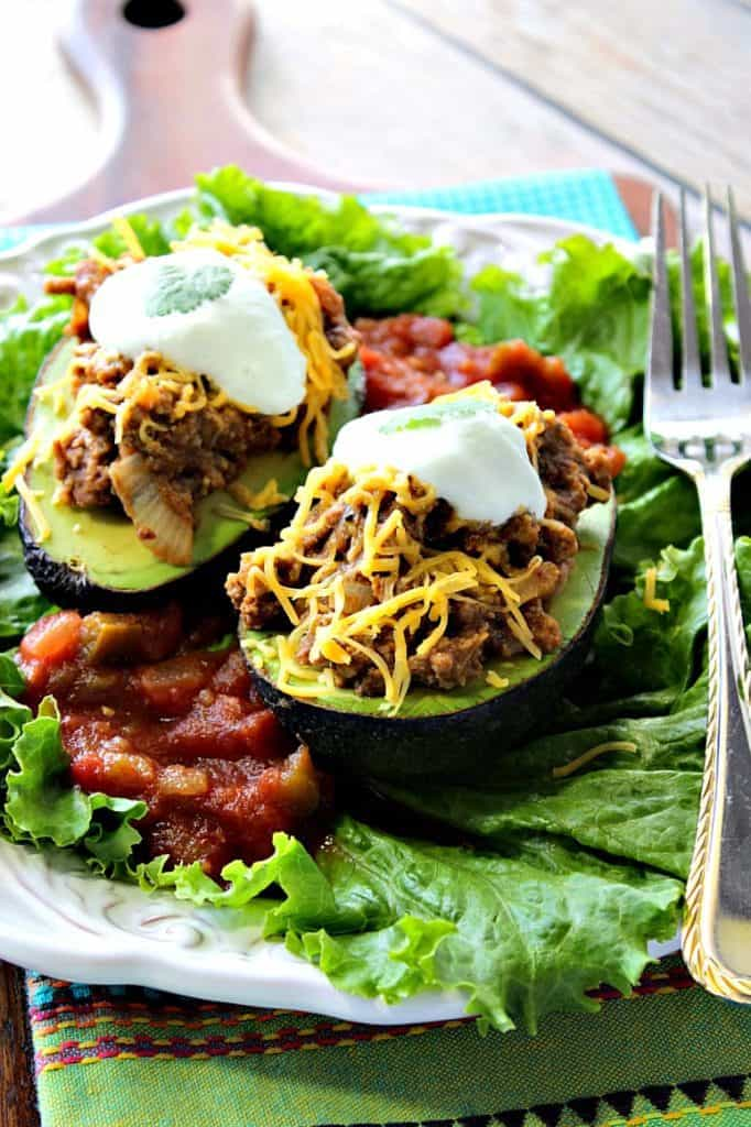 Vertical image of two stuffed avocados on a bed of lettuce with cheese and sour cream on top.