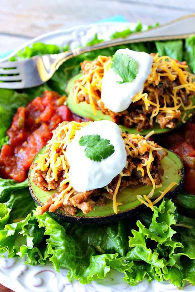 Vertical closeup image of two stuffed avocados with ground turkey, shredded cheese, and sour cream.