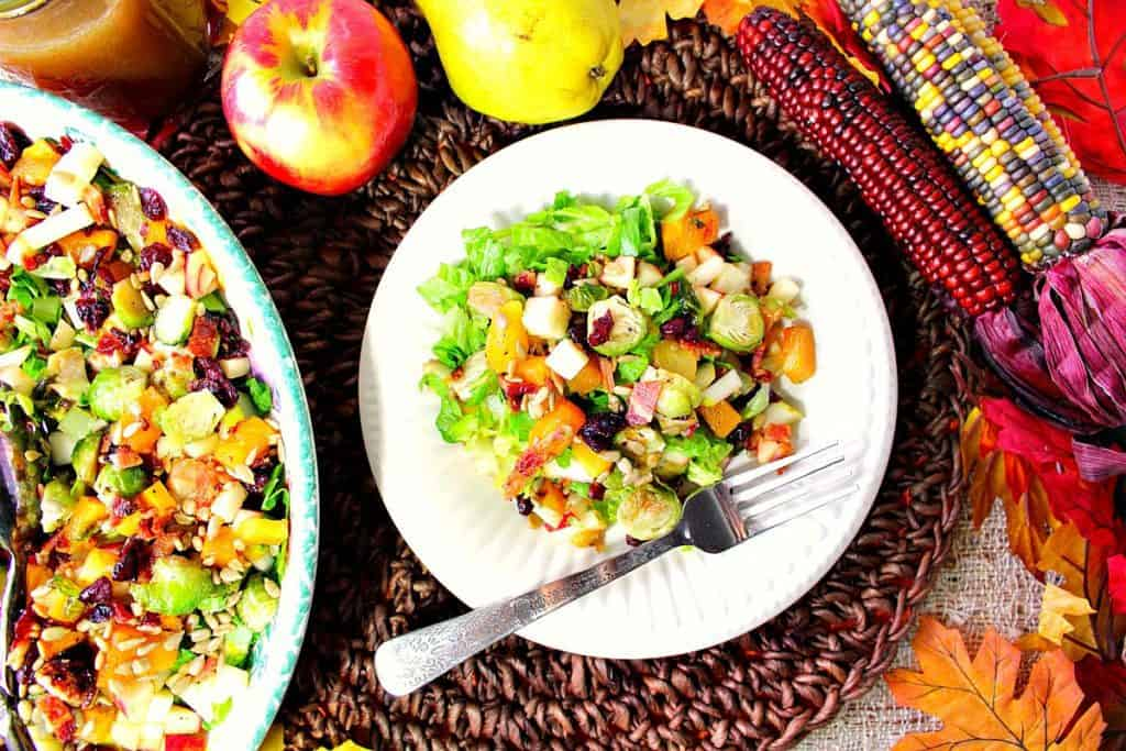 Overhead photo of a fall chopped salad on a plate with fork. Indian corn and fruit surround the plate.