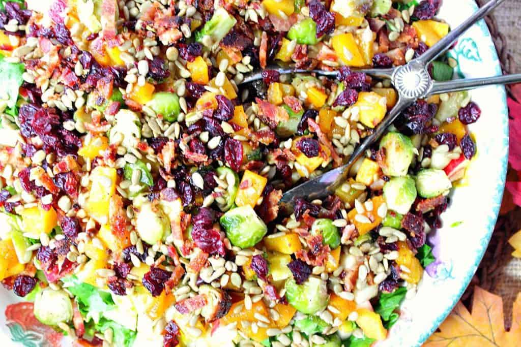 Overhead colorful photo of a fall chopped salad with tongs and jewel tone veggies and fruit.